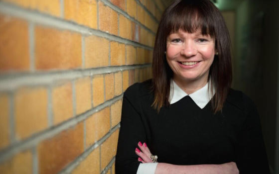 Dr Deborah O'Neil is wearing a black jumper with white collar and standing against a brown brick wall. She had dark brown hair to her shoulders and a fringe.