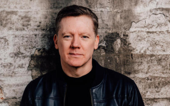 Fergus Linehan has short brown hair and is wearing a leather jacket standing outside against a wall