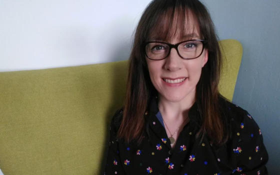 Dr Siobhan O'Connor is wearing a floral blouse and has long dark hair and dark glasses. She is sitting on a yellow sofa