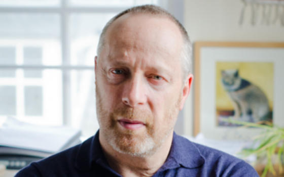 Close up of Professor Stephen Reicher FRSE wearing blue collared top. Stephen has a beard and close cropped hair.