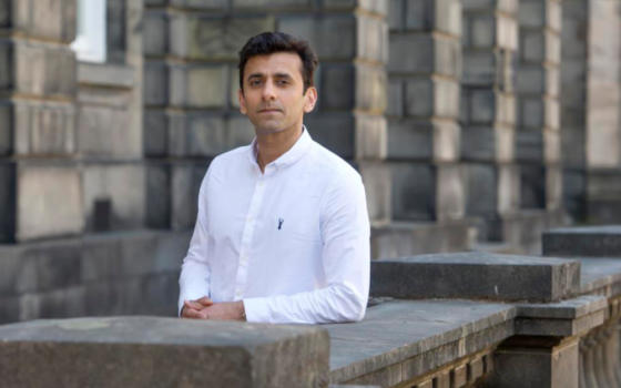 Professor Nasar Meer is wearing a white collarless shirt and leaning against a wall outside