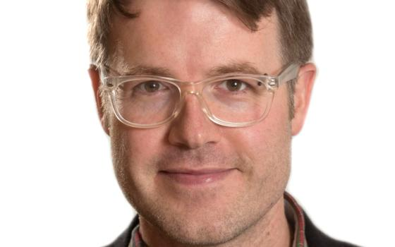 Image of Professor Matthew Chrisman. He has short brown hair and clear framed glasses and wears an open neck shirt with a t-shirt underneath and a jacket