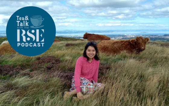 Dr Stella Chan is sat in on a hill in front of a herd of highland cows - she is wearing a pink jumper with a flower knee length skirt