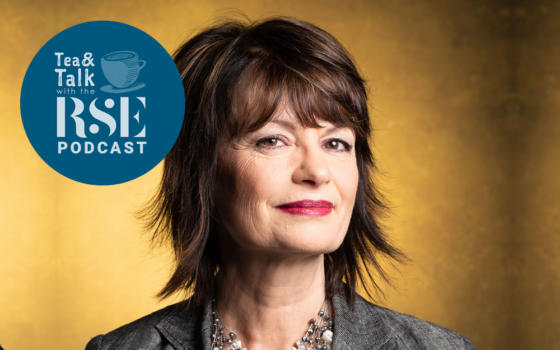 Professor Anne Glover has short, feathered dark hair and is wearing a grey jacket and necklace, against a gold coloured background. The Tea and Talk podcast logo is to the left of her face when looking at the photo straight on.