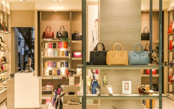 A picture of luxury items such as handbags in a pristine shop.