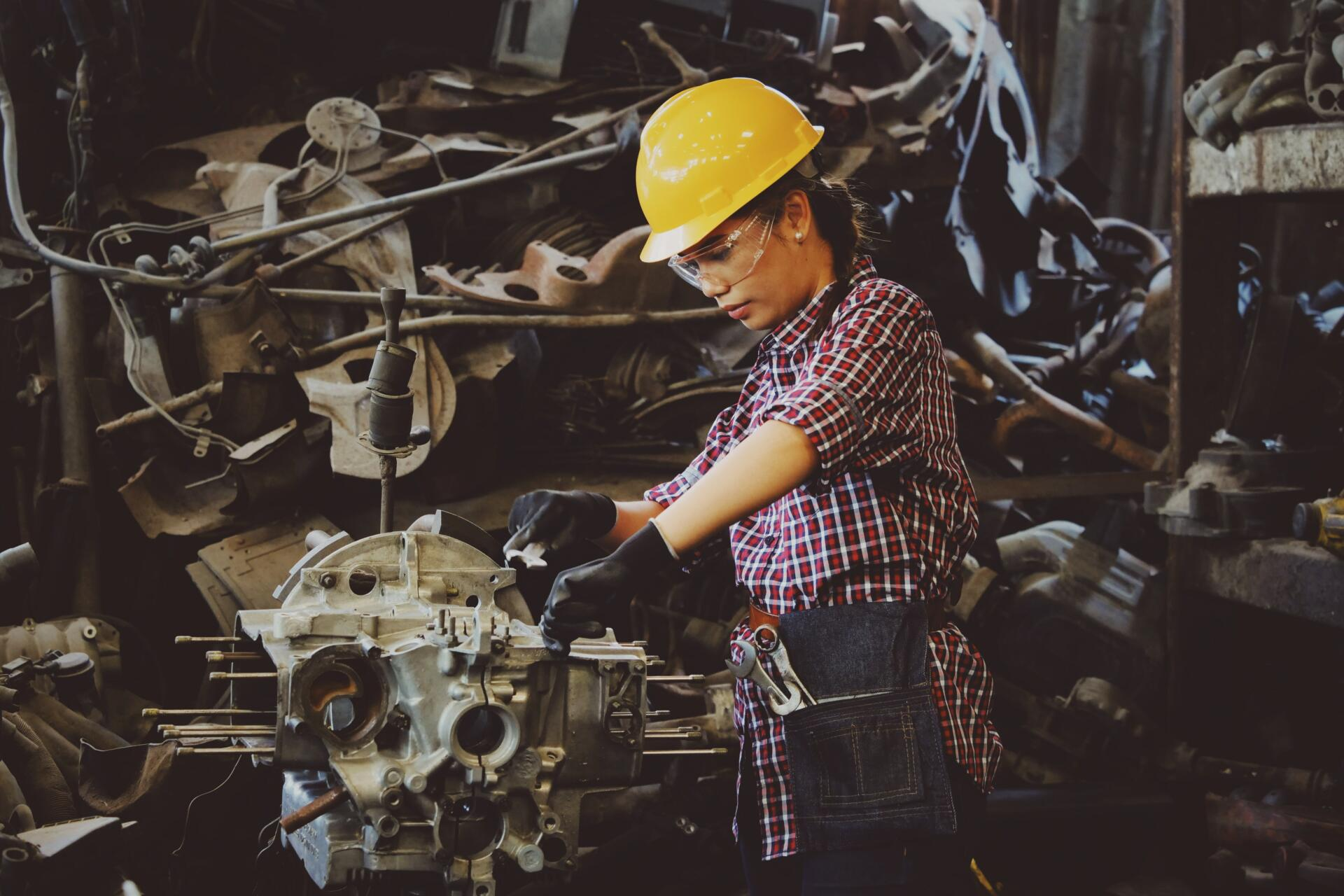 A woman in a checked shirt and a hard hat works on part of a machine.