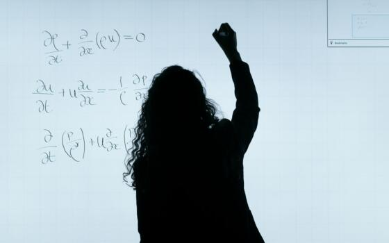 The silhouette of a woman is visible writing equations on a white board.