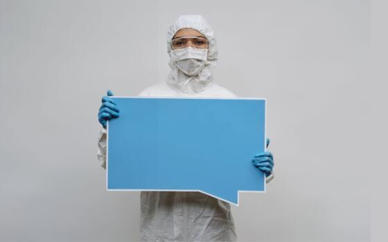 A figure in full PPE including blue gloves and a face mask holds a large blue speech bubble.