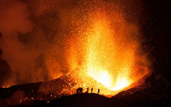 Figures are silhouetted in front of a volcanic eruption.