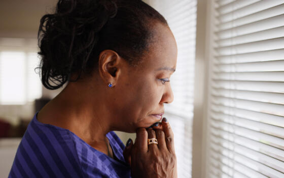 A black adult woman looks sadly out of a window.