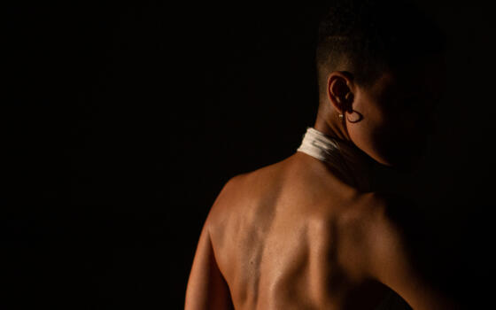A woman's bare back is lit from the side