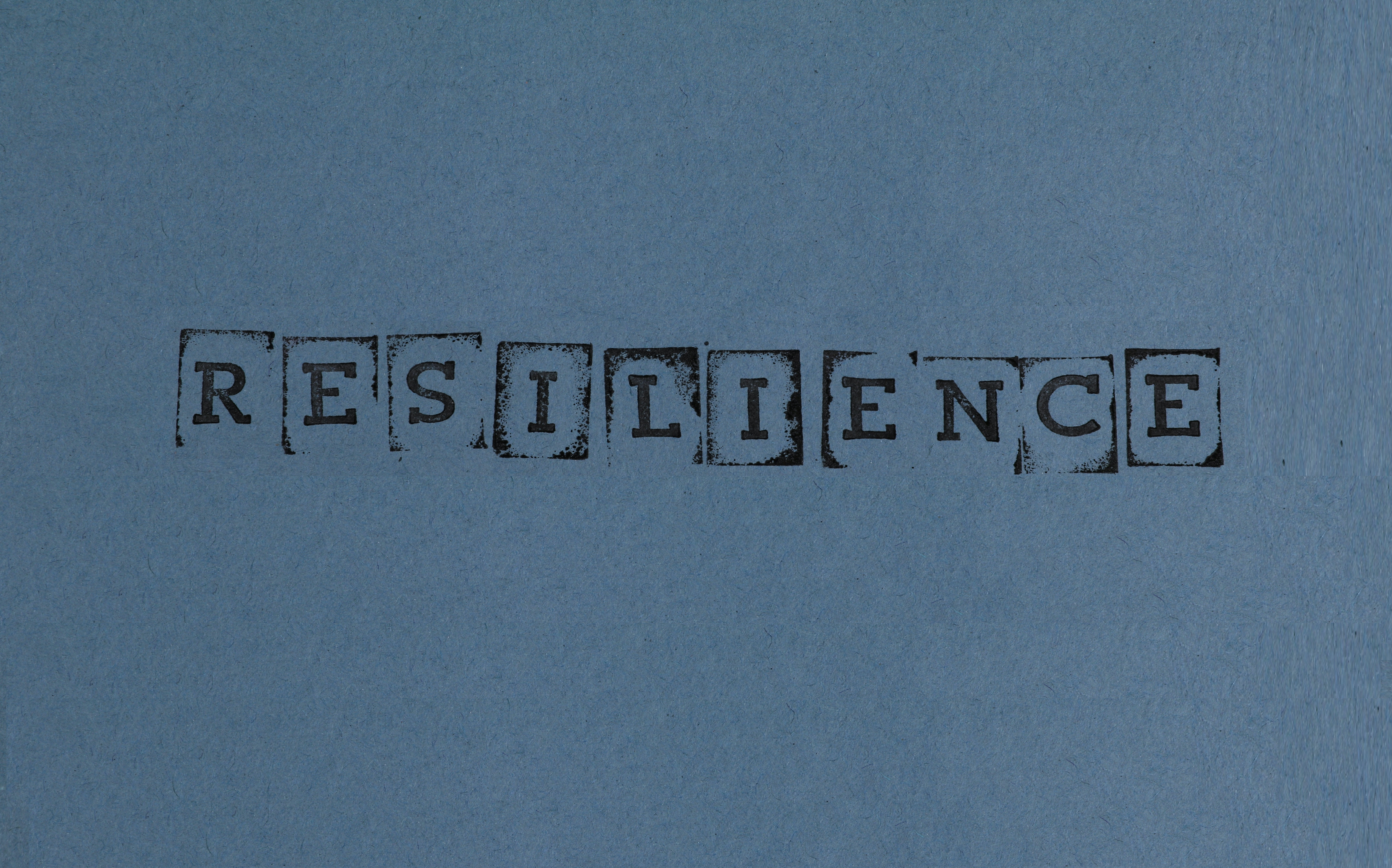 The word resilience is stamped on blue paper
