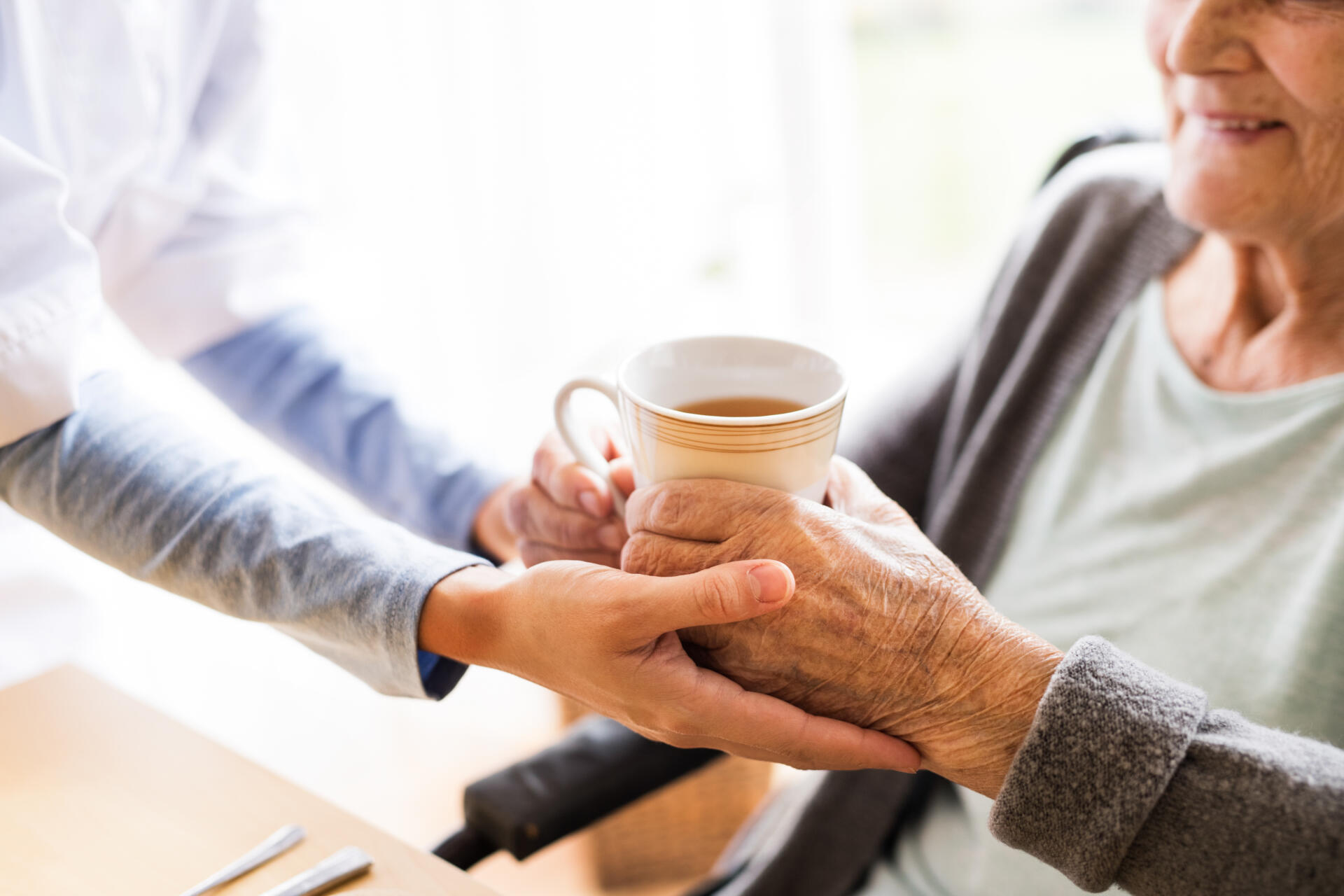 A woman's hands support an eldery person holding a cup of coffee.