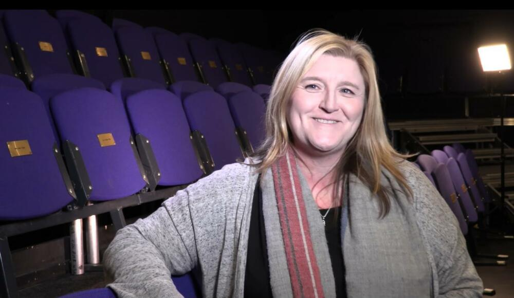 Lead artist Nicola McCartney stands in front of empty chairs smiling at the camera.